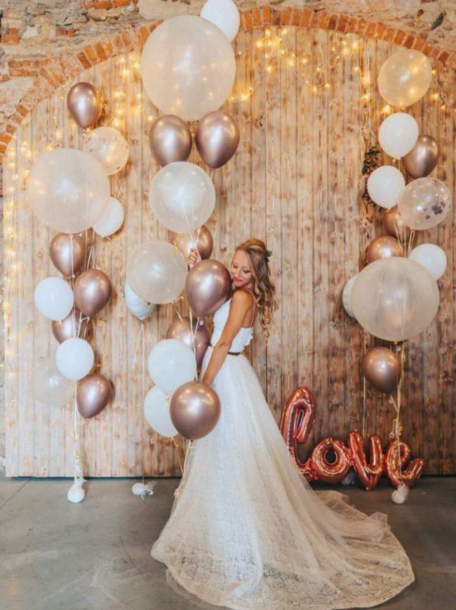 Krásná svatební dekorace složená z organických trsů balónků s héliem s prvky chromových balónků.