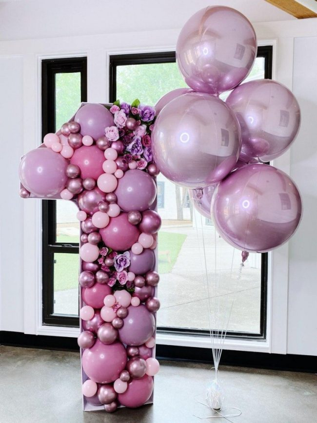 Růžové mosaikové písmeno z malých balónků a balónky s héliem