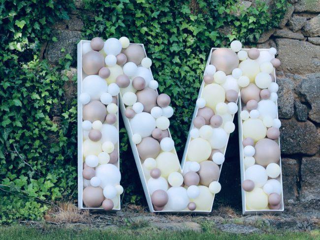 Mosaikové písmeno M z malých balónků decentních barev vhodné na svatby a oslavy narozenin